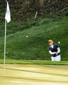 Golfspiller som slår mot hullet