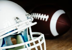 Hvit ameriaknsk football hjelm og football i bakgrunnen